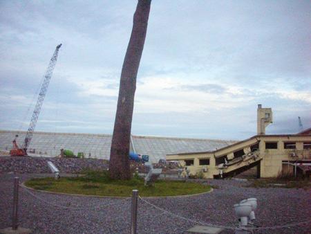 写真 2=「奇跡の一本松」と被災建物(陸前高田ユースホステル)、新堤防。