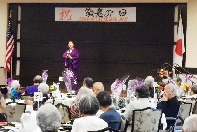10年以上にわたって、敬老の日昼食会のエンターテインメントを提供している佐藤よしえさんは、今年は「まつの木小唄」と「下町育ち」を歌いました。9月8日、練尾(ねりお)ダイニングルームで。(Cultural News Photo)