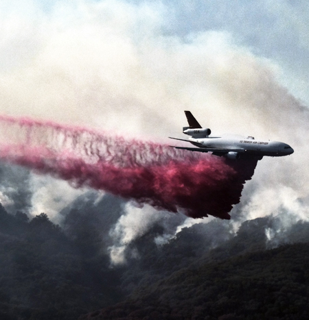 A firefighting DC-10 makes a fire retardant drop over a wildfire in the mountains near Malibu Canyon Road. (Associated Press, Nov. 11, 2018)